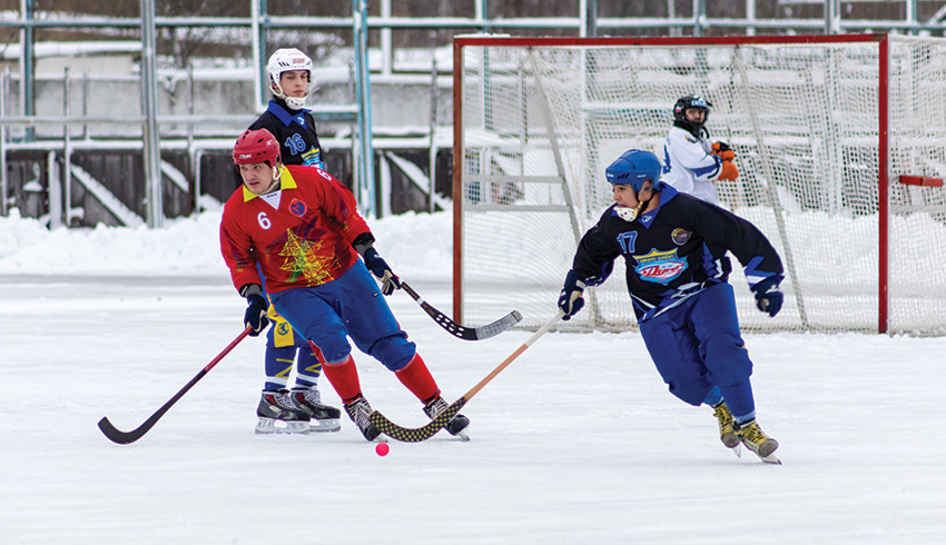 two bandy sportists cruising the rink to score