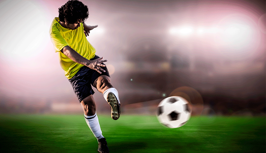 brazilian football player kicking ball in the pitch