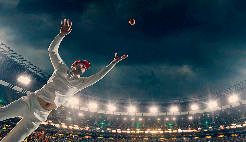 cricket player flying to catch the ball