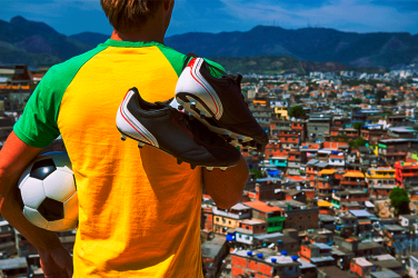 young football player with boots and a ball in his arms looking at the skyline