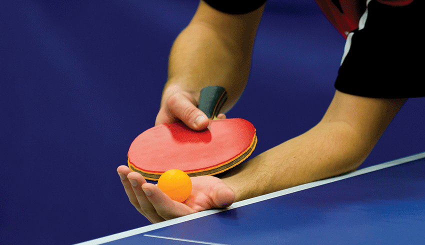Table tennis player ready to serve the ball during match
