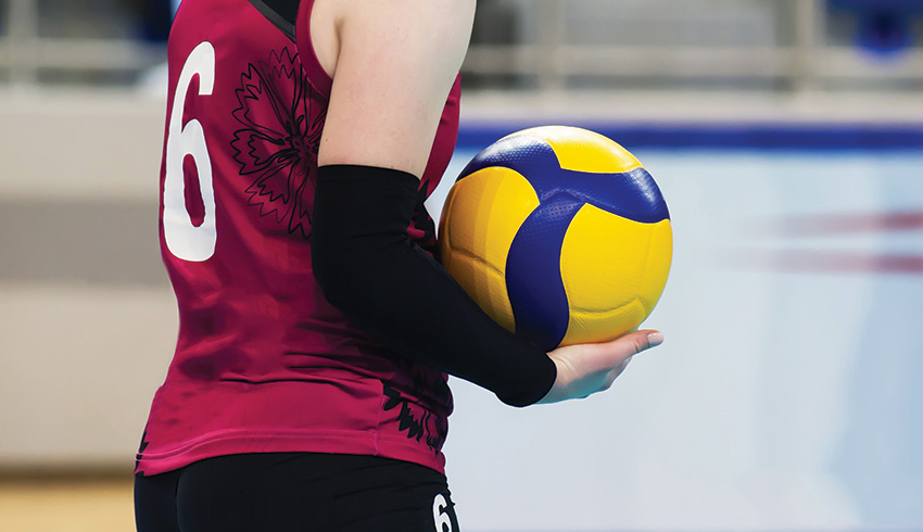 Volleyball player holding ball in a women's match